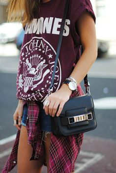 ramones tshirt tucked into jean shorts with plaid/flannel collared button up shirt wrapped around waist and black shoulder purse..