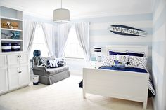 A surfer toddler room. I used a pale blue and white color palette and accented the room with ssailboats, a boat helm, anchors, and other nautical elements.