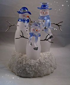 """Delightful Glass Winter Decor of a Snow Family! This lighted (with a battery) snow family is in perfect pre-owned condition: no chips or cracks. Stands 7 1/2"""" tall by 6 1/4"""" wide at the base. The snow men are a frosted glass with metal arms and blue glass mufflers and hats. The base resembles snow, of course! Has an 'on/off' switch for the battery. Perfect decor for any spot in your house! Comes in the original box which will be boxed again for shipping USPS Priority Mail."""