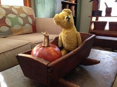 little old doll cradle, old bear on top small old table in brown paint.