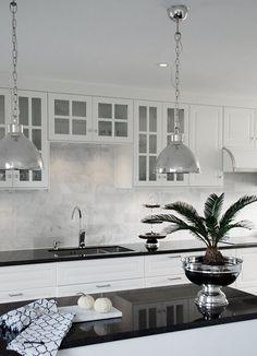 """Kök med lampa """"Monterey"""" ovanför köksö. Svarta bänkskivor i granit. Carraramarmor på väggen. Champagnekylare. www.longcoastliving.se"""