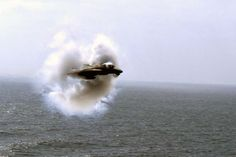 F-14 Tomcat breaking the sound barrier over water.
