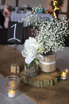 """Rustic Babys breath and log slice center pieces. My friend loaned us the burlap runners from her wedding. My brother in law cut log slices, 8-10"""", for each table. Three smalls jars (votive holders, baby food jars, and jelly jars) were decorative with ribbon and twine and held a battery powered tea light candle. A small mason jar was filled with pebbles and one flower. One large mason jar was wrapped in burlap and ribbon and help 3 stems of babys breath."""