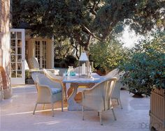 Surrounding a limestone-and-marble dining table are Nice chairs by Janus et Cie.