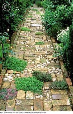 レンガや石を組み合わせ、ところどころにグランドカバーの植物を植えてリズム感のあるアプローチに。