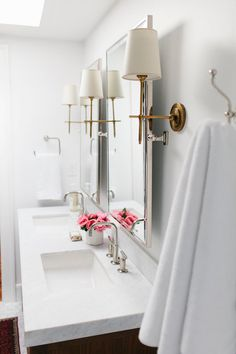 Brass sconces in a bathroom with white paint are a sophisticated aesthetic for any home!