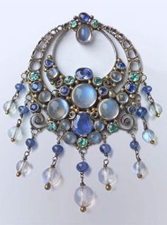 An Arts and Crafts brooch, by Dorrie Nossiter, British, circa 1930. Composed of silver, gold, sapphires, tourmalines and moonstones.