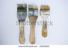 Used artist brushes prepared for painting on white canvas