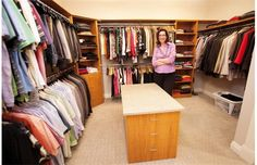 """Kristie Demke in the master bedroom's sizable walk-in closet, which includes an """"island,"""" perfect for laying out outfits or ironing."""