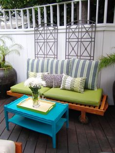 The bright aqua table give this outdoor patio a nice pop. We also really like the striped back pillows with the solid cushions.