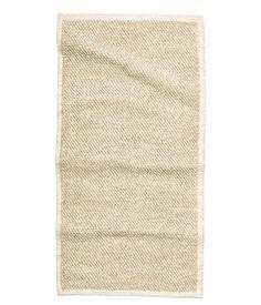Vaaleanbeige. Suorakaiteen muotoinen matto kudottua villa-puuvillasekoitetta.