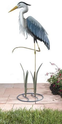 "Metal Heron with Stand . $64.95. This durable backyard decoy makes both an elegant focal point in your garden and helps to protect your pond from similar preditors. It can be secured with two prong metal stake or used free standing with the decorative stand. This high quality Heron is handcrafted in metal and painted with automotive paint for a lasting finish. Makes a great gift for anyone with a pond. 16"" W x 40"" H"