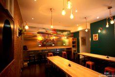 Matériaux bruts, couleurs dynamiques et luminaires cuivrés pour ce restaurant au style industriel et pop.