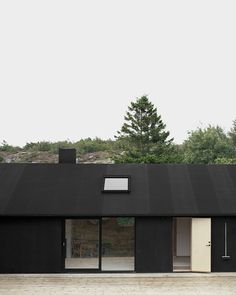 Plywood cladding, coated in black pine tar the way boats are preserved. Tar paper roof with plywood eaves and integrated aluminum gutters, coated in black.