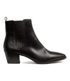 Black. Ankle boots in imitation leather with covered elastic side panels and pointed toes. Satin lining, imitation leather insoles, and rubber soles. Heel