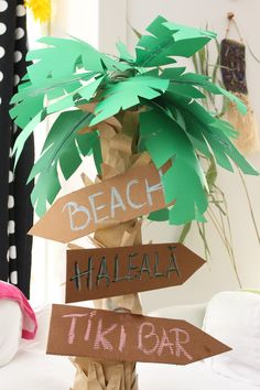 Paper palm tree for luau party decoration (with pizza cardboard signs). Made with wrapping paper on a big lamps leg and leaves out of craft paper and florist wire.