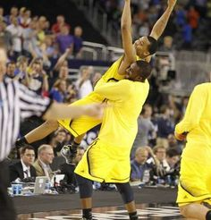 Michigans Trey Burke is lifted in the air by Corey Person after their overtime win over Kansas in the South Regional of the NCAA tournament .