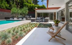 This mid century in Hollywood Hills by Edward H. Fickett has some unique features. The white sculptural wall on the inside mimics the wall in the front