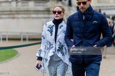 Olivia Palermo wearing total look Moncler Gamme Rouge a white jacket, black turtleneck red sunglasses and grey pants and Johannes Huebl wearing a navy quilted jacket with pocket square outside Moncler Gamme Rouge during the Paris Fashion Week Womenswear Fall/Winter 2016/2017 on March 9, 2016 in Paris, France.