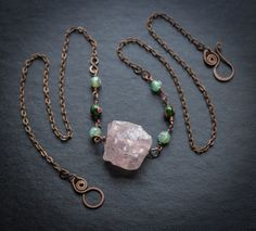 A simple, powerful necklace, weighted with a sizeable hunk of lovely Turkish Delight Rose Quartz, flanked by hand wrapped rosary style chain made of delicate rosette-adorned glass beads. This necklace measures 27 long and closes with a hook and eye shape in my Bird Mother shape, inspired by prehistoric bird goddess imagery. Rose quartz is said to correspond to the heart chakra and have lots of loving vibes-- this one almost glows with them