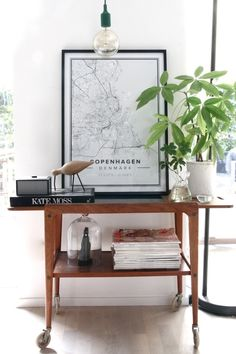 Many interior bloggers revamp their vintage drink trolleys by putting a city map above or right on it. Most choose a shiny black frame and add green plants for a classy and fresh look.