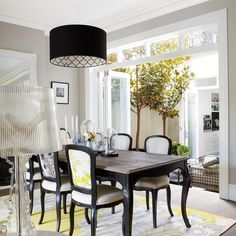 Yellow and black dining room features a black drum pendant illuminating a black French dining table with cabriolet legs and a wood top lined with black and white french dining chairs atop a white and yellow floral rug placed in front of glass folding doors which open to the sunken backyard.