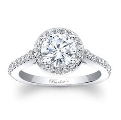 Stunning, in vogue, this white gold diamond halo engagement ring will capture the eye of many admirers. Shared prong set diamonds encircle the round diamond center and cascade down the dainty shank for a look of sheer elegance.<br /> <br /> Also available in 18k and Platinum.