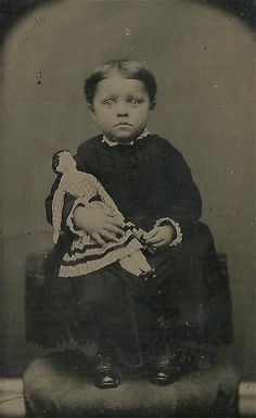 Antique photo of bright-eyed little girl and her doll. This photo appears to be very early, circa 1880 - 1900.