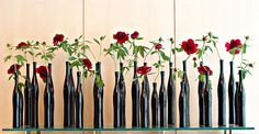 take empty, clean wine bottles, spray paint black and put single roses in each