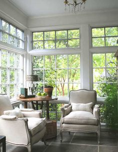 An antique table is paired with two Belgian club chairs in a Swedish-inspired conservatory.