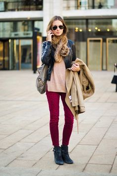 Dark red skinny jeans paired with tan sweater and black leather jacket and black booties