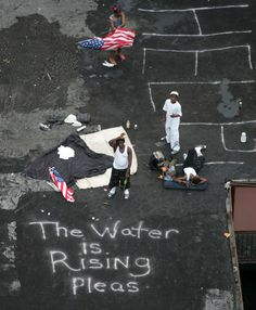 Residents wait on a roof top to be rescued from the floodwaters of Hurricane Katrina in New Orleans, September 1, 2005.   Photo credit: REUTERS/David J. Phillip/Pool DJP/mk