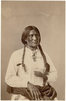 Studio portrait of the man Si-ha-tan-ka or Big Foot in partial Native clothing, seated in fringed posing chair, wrapped in blanket with quilled or beaded blanket strip; wrapped braids; wearing large metal cross Culture/People:Minneconjou Lakota (Minniconjou Sioux) Date created:May 1872