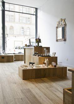 område med udstilling af interior/objekter i forskellige niveauer og lamper hængende over.