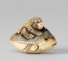 An ivory netsuke of a monkey on a fugu. 19th century. A monkey in a sleeveless jacket riding a blowfish (fugu), the fish's tail held to the side. Pupils of black glass. Inscribed Masanao.