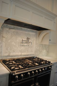 Gorgeous close up shot of a black, French stove with towel rail flanked by white marble counters with a marble herringbone tiled backsplash above featuring a marble molding framed swing arm pot filler below a paneled stove hood with corbel supports. Grey Backsplash, Beadboard Backsplash, Herringbone Backsplash, Kitchen Backsplash, Backsplash Ideas, Pot Filler, Gambrel, New Kitchen, Kitchen Mantle