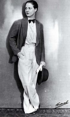The actress Charlotte Andler in 1929. Jacket, trousers, shirt, bow tie, gloves. Male wardrobe enters the female cloakroom.