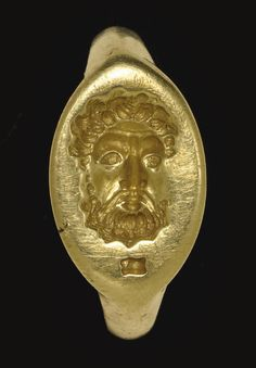 A GREEK ELECTRUM FINGER RING   CLASSICAL PERIOD, CIRCA 4TH CENTURY B.C.   Stirrup-shaped, flattened at one end, the plain hoop bevelled on the interior, rounded on the exterior, the pointed oval bezel bevelled on the underside, the upper surface engraved with a three-quarter frontal head of a bearded man with curly hair, furrowed beard, large almond-shaped eyes and down-turned mustache, an astragalos (knucklebone) in the field below