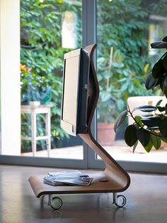 Cobra / Design: Mario Bellini, 2006 / Cobra is a dynamic TV stand, both from a visual and usage standpoint, built with curved plywood polished entirely by hand and featuring brake-fitted wheels and mood lighting, which is projected on the floor. Equipped with multiple sockets to power the eventual audio-visual components to set on the shelf, it features a hidden and discreet cable inlet that connects them to the video signal.