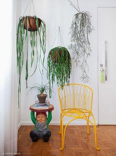 Entrada da casa com parede repleta de plantinhas, banco gnomo de Philippe Starck para a Kartell e cadeira amarela.