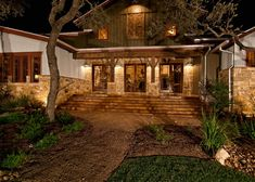 Exterior entry to the ranch foreman's house, which showcases 200+ year old timbers, wood windows, dry stacked stones, a tin roof, and handmade barn doors. Texas Custom Home Builders | Todd Glowka Builder, Inc.