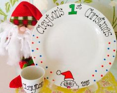 Putting out the mince pie and drink for Santa and a juicy carrot for Rudolph is an important event in every childs Christmas Eve tradition. Why not do it in style with one of our hand painted, personalised plates and mini mug?  These plates are made to order and can be personalised with up to 4 childrens names, or one family name.  Plates can read either TO SANTA or TO FATHER CHRISTMAS. Please stipulate when ordering.  ***** ALSO AVAILABLE IN WELSH *****  Plates are for decorative purposes…
