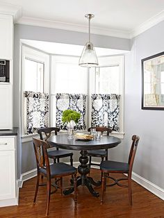 A casual dining area is tucked away to the side of the kitchen. Despite the small sizes of the kitchen and dining areas, the separation allows each space to have its own purpose. The three-window bay gives the space a cozy, comfortable feel. Curtained panels add color and provide privacy, while the tops of the windows are left undressed to let light in.