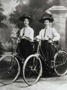 Edwardian ladies stand for a portrait with their bicycles