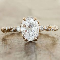 This 14k yellow gold ring by Ken and Dana Designs highlights an oval diamond with two round stones on either side, as well as a twisted band that's sprinkled with brilliant white diamonds.