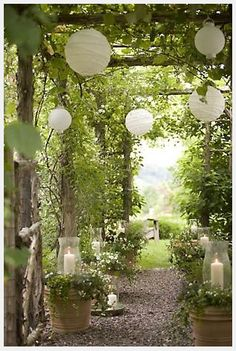 adding paper lanterns to any outdoor location can add such a magical whimsey! Love this landscape. Pretty candles put into the potted greenery. A post on lots of Spring Ideas for backyard landscapes