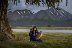 The shaman Galba plays a ritual drum beneath the tree in the Altai Mountains that marks the place of her birth. Galba was a member of Mongolia's small Uriankhai ethnic minority; most Uriankhai live in China.