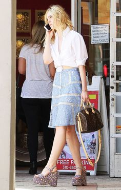 Elle Fanning wears white button-down shirt tied at the front, lace skirt, printed wedges, and a Louis Vuitton bag