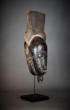 Afrikaanse Tribal MBLO BAOULÉ masker. Ivoorkust.  Hoogte 50 cm.Breedte 20 cm.Hout kaolien en zwart pigment.Geleverd met een aangepaste zwart geschilderde houten en metalen staan.Mblo is de naam van een categorie prestaties die gebruikmaakt van gezicht maskers in sketches en solo dansen. Mblo maskers gebruikt in entertainment dansen zijn een van de oudste van Baule kunstvormen. Deze verfijnde menselijk gezichtsmaskers zijn meestal portretten van bepaalde bekende personen. Mblo maskers…