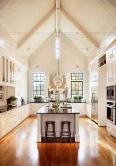 Kitchen with traditional cabinets designed in high ceiling interior with  modern island, appliances and lightnings.. Mix is grounded by simple an strict color palette.. and looks really amazing!